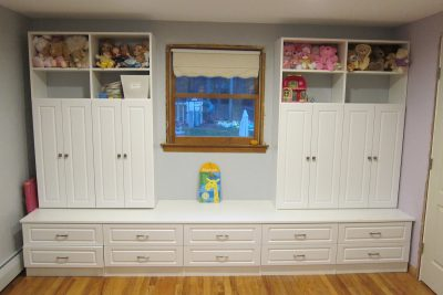 Custom built-ins and cabinets - Upper shelving, double cabinets and a bank of drawers help keep a child's play area organized.