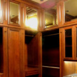 Largewood walk-in closet fabricated in solid wood, with floor-to-ceiling storage options and mirrored upper cabinets.