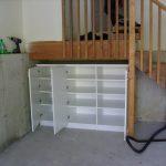 Understair Storage - White melamine storage space under garage entryway staircase.