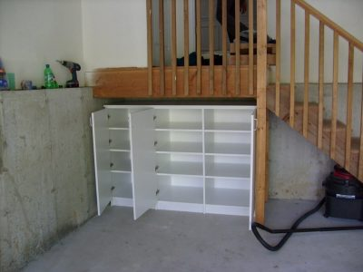 Understair Storage - White melamine storage space under garage entryway staircase.